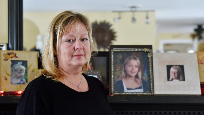 Marcia Perryman stands for a portrait, flanked by photographs of her daughter Olivia, in her York Township living room Wednesday, Jan. 27, 2016. Olivia, 14, died by suicide Jan. 18.