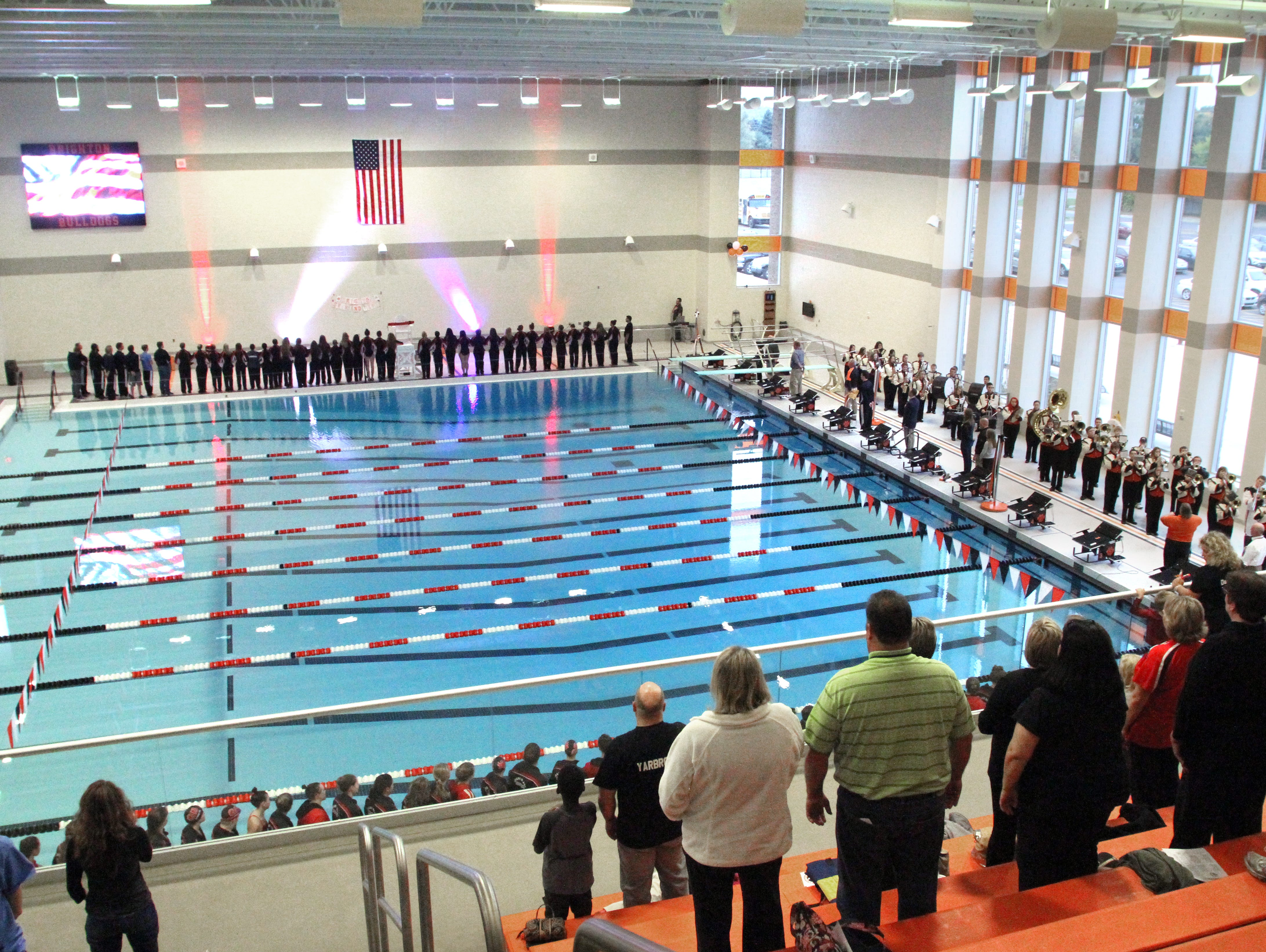 Spectators stand as the national anthem is played by members of the Brighton High School marching band at the opening of the new pool at Brighton High School on Tuesday.