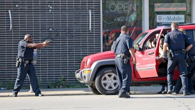Milwaukee police take a man into custody on Aug. 14, 2016.