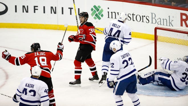 New Jersey Devils right wing Nick Lappin (36) and teammate center Travis Zajac (19) celebrate Lappin's goal on Toronto Maple Leafs goalie Jhonas Enroth, right, of Sweden, during the third period of an NHL hockey game, Wednesday, Nov. 23, 2016, in Newark, N.J.