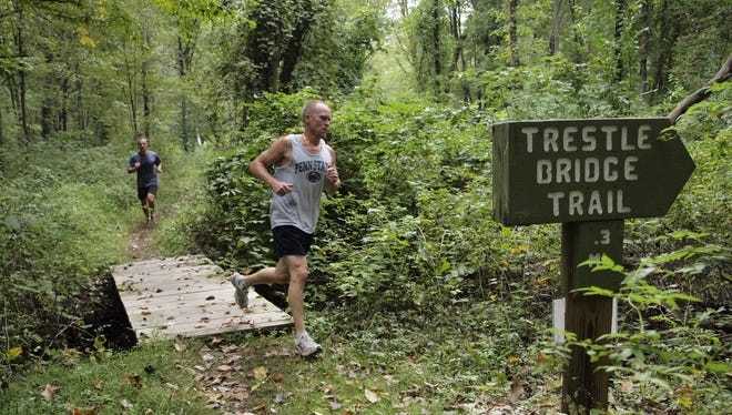 """Runners cross into the Trestle Bridge Trail during a """"Trial of the Trails Run"""" at the Demarest Nature Center in 2010. The Borough Council passed a 20-year management agreement with the nature center on Nov. 28."""
