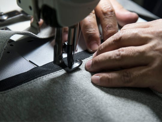 Tito Almachi, a tailor, works on a chair at Gordon