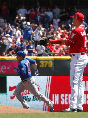 Cubs catcher Miguel Montero rounds the bases past Reds starting pitcher Anthony DeSclafani after Montero hit a solo home run in the second inning Sunday at Great American Ball Park