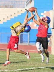 Isaac Brown catches a ball over a teammate during Indio High School's football practice, August 17, 2017.