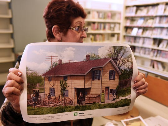 Mazzeo holds a photograph of the home that Douglas nearly lost for unpaid property taxes in 1949, when he was 106. A publicity campaign led by Bergen County's chief of detectives and the publisher of The Bergen Evening Record raised enough money to let Douglas stay in the home.