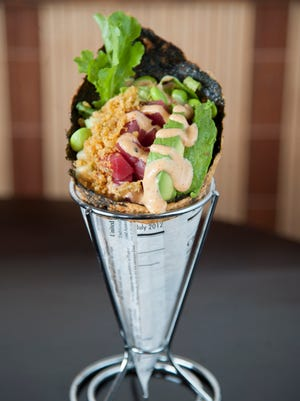 Special Roll A  (tuna, cucumber, avocado, romaine, edamame, tempura crunch, and spicy mayo sauce) is served in a in house-made seaweed chip cone at Oki Maki in Voorhees.