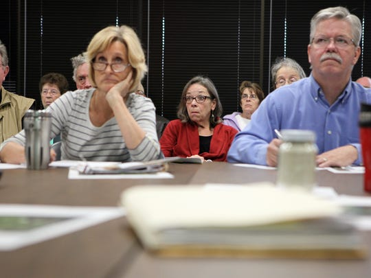Kathy Kachel, center, a Wisconsin homeowner whose house overlooks Pattison Sand's Iowa operations, reacts to testimony given by professor Patrick O'Shaughnessy at a meeting of the Mine Reserve Expansion Study Committee. In the foreground are commitee members Anne Osmundson  and Tom Blake.