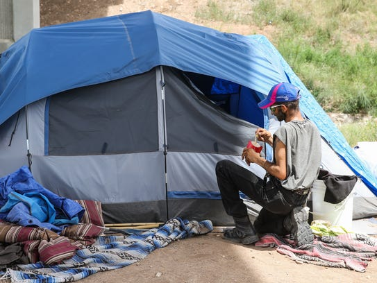 Reggie Felton, eats near his tent at a tent city under