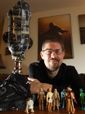 Brian Kleis of Coralville poses with his Star Wars-themed prosthetic leg and original Star Wars memorabilia on Tuesday, Dec. 15, 2015. The long-time Star Wars fan received the prosthetic leg in April after an infection spread and required part of Kleis' leg to be amputated.