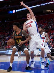 Hawks forward John Collins is defended by Pistons forward Henry Ellenson in the second half of the Pistons' 109-87 exhibition win on Friday, Oct. 6, 2017, at Little Caesars Arena.