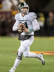 Michigan State quarterback Brian Lewerke (14) drops back for pass in the first quarter on Saturday, Oct. 14, 2017, in Minneapolis.