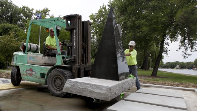 Matt Carrell (left) and Tony Vickman of Miron Construction move a monument dedicated to veterans into position on the Isle of Valor in Menasha. The monument was moved Monday from its location at the Menasha Public Library. The Isle of Valor is located at 640 Keyes St.