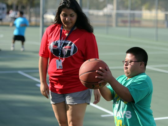 Immokalee High student Marisela Chaparro, left, helps coach Special Olympics athlete Kiko Diego during basketball practice at Immokalee High School on Nov. 29, 2016. It's part of Project UNIFY — a Special Olympics inclusive program incorporated into five Collier County high schools, including Immokalee High, seven middle schools and six elementary schools.