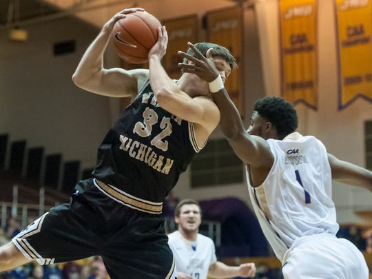 Western Michigan guard Taylor Perry (32) gets tangled up with James Madison guard Shakir Brown (1) while pulling in a rebound during the first half of an NCAA college basketball game in Harrisonburg, Va., Thursday, Dec. 3, 2015. (Daniel Lin/Daily News-Record via AP) MANDATORY CREDIT
