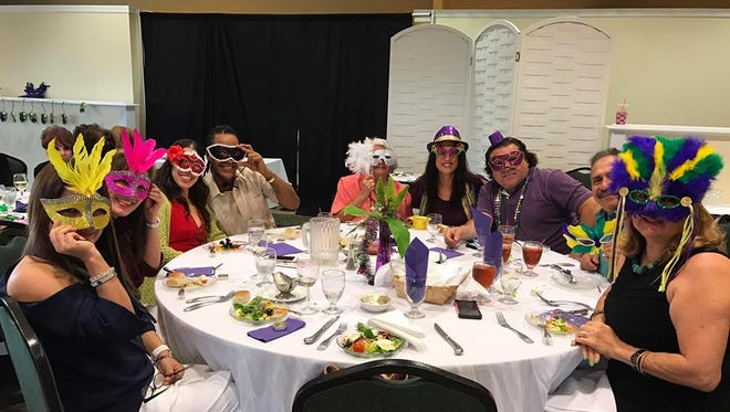 Members celebrate a Mardi Gras theme at the Pan Am Round Table's annual fashion show.
