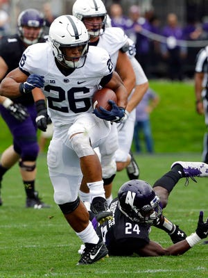 Penn State running back Saquon Barkley (26) runs for a touch down past Northwestern corner back Montre Hartage (24) during the second half of an NCAA college football game in Evanston, Ill., Saturday, Oct. 7, 2017. Penn State won 31-7. (AP Photo/Nam Y. Huh)
