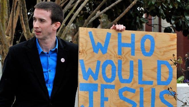 Ross Reddick, a Presbyterian minister from Sylacauga, Ala., holds a sign during a rally concerning predatory lending legislation Feb. 4, 2014, in Montgomery, Ala.