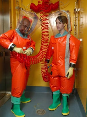 The Centers for Disease Control and Prevention has suspended work in its biosafety level 4 laboratories while it investigates potential issues with hoses that provide researchers with purified air. Lab workers in this CDC file photo are shown attaching breathing air supply hoses to the full-body protective gear they wear when working with the world's most dangerous pathogens.