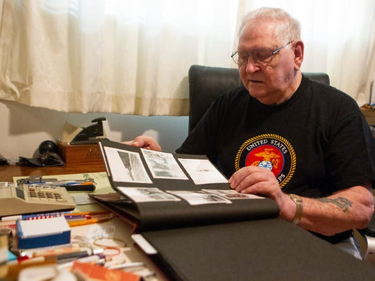 John Zwolinski flips through a scrapbook of photographs containing the plywood painting that was modeled after him.