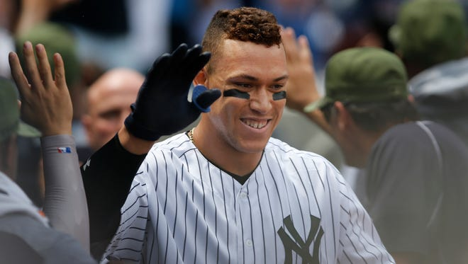 New York Yankees celebrate with the Yankees' Aaron Judge after he hit a third-inning, grand slam in a baseball game against the Oakland Athletics in New York, Sunday, May 28, 2017. (AP Photo/Kathy Willens)