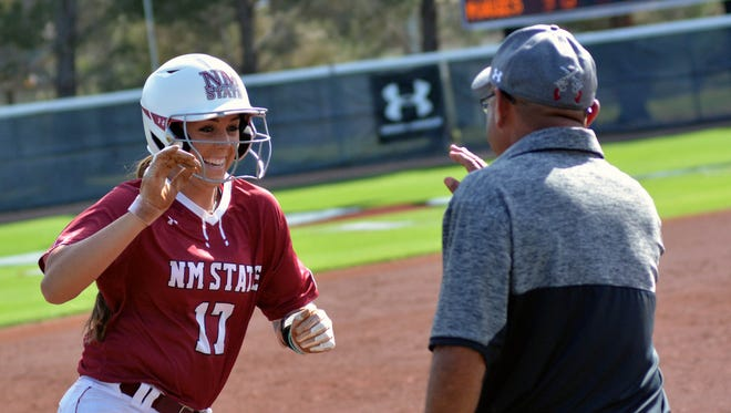 Kelsey Horton gets congratulated by Aggie Assistant Coach Thomas Ramos after hitting a two run homer in the bottom of the second inning in the first game against Seattle University on Saturday.