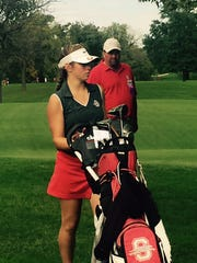 Shelby coach Brad Ruminski approaches the 18th green Saturday with his daughter Amanda as she finishes her round of 74.