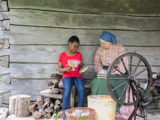 Tyler learns how to card wool at Old World Wisconsin