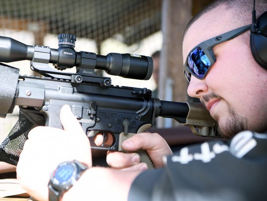Javier Moraga fires an AR-15 at the Wayne E. Smith