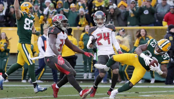 Green Bay Packers running back Aaron Jones (33) dives into the end zone for the game winning touchdown in overtime against the Tampa Bay Buccaneers on December 3, 2017, at Lambeau Field in Green Bay, Wis.