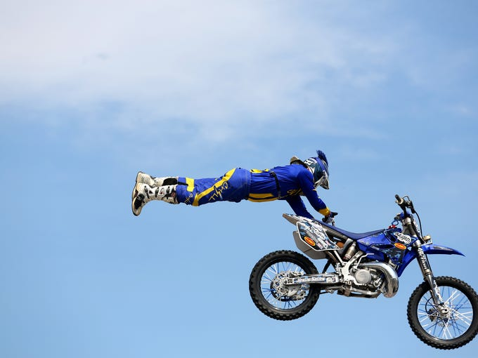 Ed Rossi from the FMZ stunt show flies high over the crowd at the Kentucky State Fair.   Aug. 15, 2014