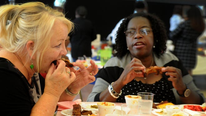 Carol Holguin (left) eats deep fried ribs with her friend Caroline McKinney (right) Saturday during the 11th annual Men Can Cook contest in Oxnard. The friendly cooking competition, which took place at Thurgood Marshall Elementary, is a fundraiser for the Xi Kappa Omega chapter of the Alpha Kappa Alpha Sorority.