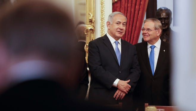 Israeli Prime Minister Benjamin Netanyahu, center, talks with Sen. Bob Menendez, D-N.J., during the start of a meeting with members of the Senate Foreign Relations Committee on Capitol Hill in Washington, Tuesday, March 6, 2018. (AP Photo/Pablo Martinez Monsivais)
