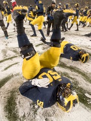 Michigan offensive lineman Michael Onwenu (50) plays in the snow after the game.