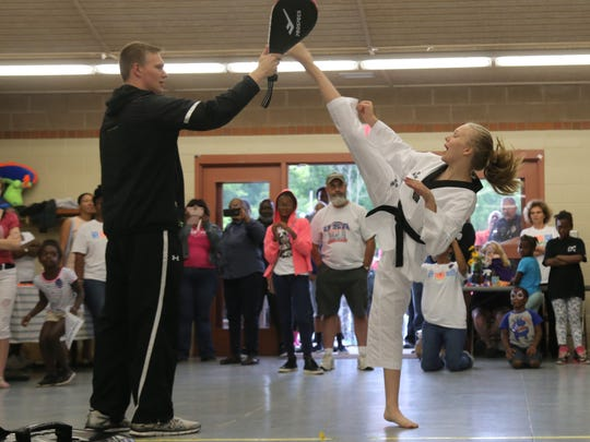Natalie Hershberger, 13, demonstates a high kick during the Safe Summer Fridays event at North Lake Park.
