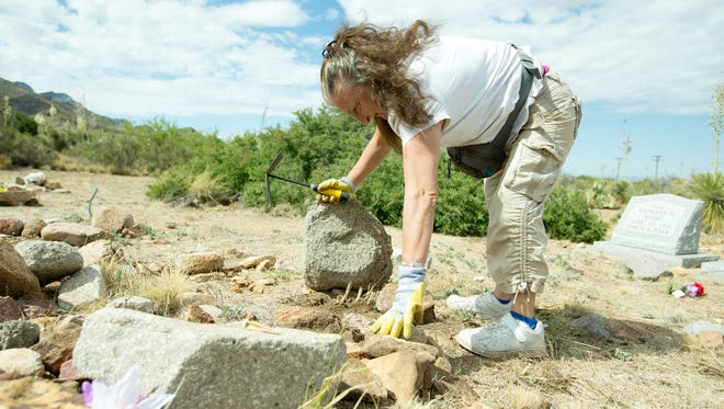 Lenore Brooker, wife of Robert Brooker, works in the Slumbering Mountain Cemetery on Saturday, June 3, 2017. Member of the Brooker family are working to preserve the cemetery.