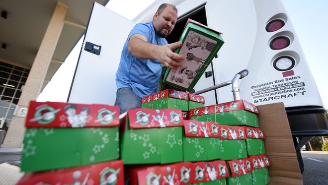 Volunteer Will McCall places a box onto a cart for Operation Christmas Child at Venture Church on Tuesday.  Boxes are filled with non-battery-operated toys, hygiene items, school supplies and simple clothing items and sent to needy children around the world.