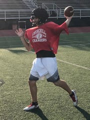 Playing catch during Sunday evening's practice is Livonia Churchill junior quarterback Drew Alsobrooks.