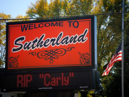 """A welcome sign in Sutherland Iowa reads 'RIP Carly"""""""