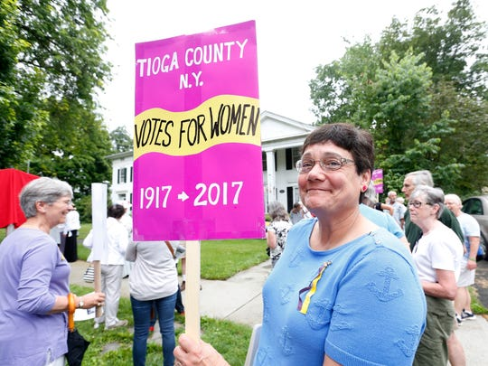 Sue Tomazic, of Owego holds a sign commemorating the centennial of the women's suffrage movement at a ceremony dedicating a marker to Elizabeth Browne Chatfield in Owego on Friday.  Chatfield was the private secretary to Susan B. Anthony from 1868-1871.