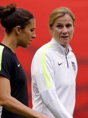 United States' Carli Lloyd, left, walks with coach Jill Ellis