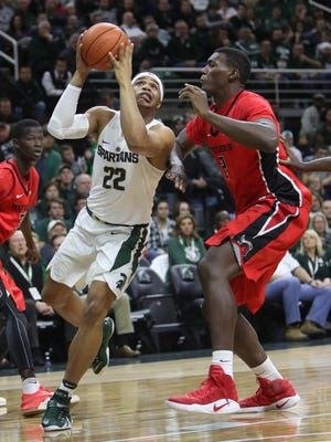 Michigan State Spartans forward Miles Bridges scores against Rutgers forward Shaquille Doorson during the first half Wednesday, Jan. 4, 2017 at Breslin Center in East Lansing.