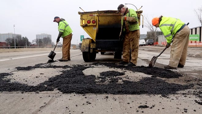 City of Southfield maintenance workers, from left, Tony Rasmussen, Jim Polk and Maxine Halperin work on patching and smoothing large pothole areas on Northwestern Highway in Southfield on Saturday. According to one study, 38% of roads in Michigan that are eligible for federal aid are in poor condition; only 17% of the state's roads were rated in good shape.Eric Seals/Detroit Free Press