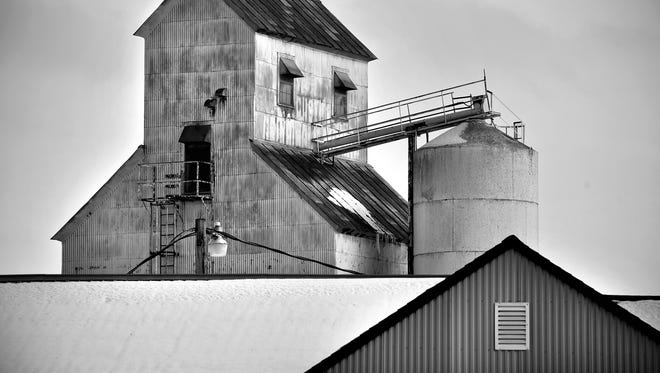 Snow-covered roof lines intersect to form symmetrical shapes at the grain elevator in Bowlus.