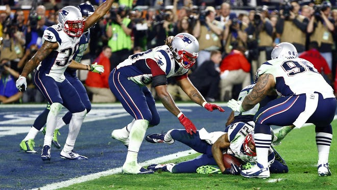 New England Patriots strong safety Malcolm Butler (21) celebrates with teammates after intercepting a pass against the Seattle Seahawks in the fourth quarter in Super Bowl XLIX at University of Phoenix Stadium
