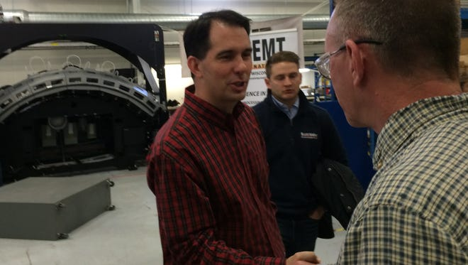 Wisconsin Gov. Scott Walker greets employees at EMT International in Hobart during a campaign stop on Friday morning.