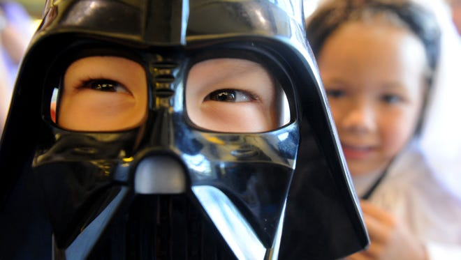"""Logan Jones, dressed as Darth Vader, and his sister Brie, dressed as Princess Leia, visit the Camarillo Public Library on Saturday for the """"Star Wars"""" Reads event. Various libraries across the country participate in the event, uniting """"Star Wars"""" fans to embrace the exploration of reading."""