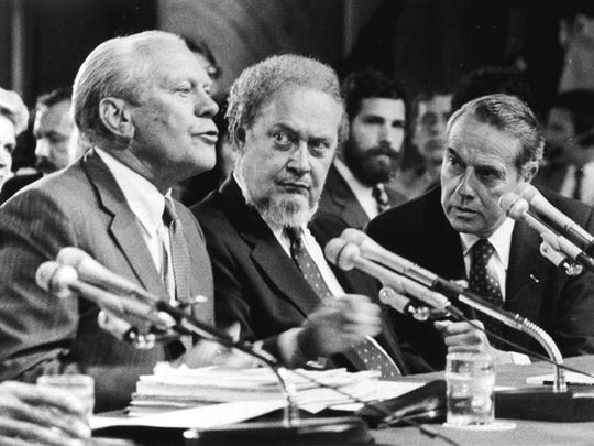 Dole looks on at right as former president Gerald Ford, left, introduces Supreme Court nominee Robert Bork on Sept. 15, 1987, as the Senate Judiciary Committee began confirmation hearings on Capitol Hill.