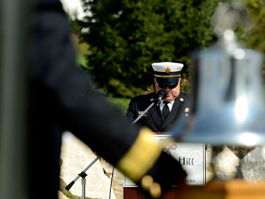Deputy Fire Chief Tony Clousher reads the names of