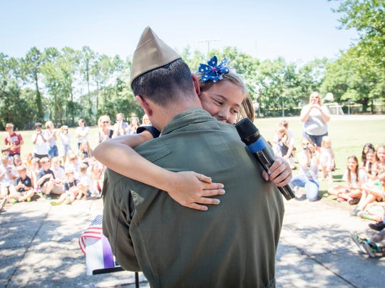 Navy Lt. Mason hugs his daughter Rhys after surprising her at the Creative Learning Center in Pensacola on Friday, May 26, 2017.  Hoyt timed his leave from Saudi Arabia to coincide with his seven-year-old daughter's last day of school.