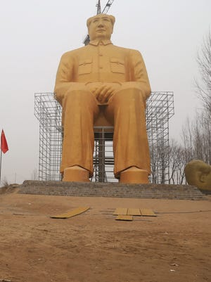 A photo of the 120-foot-high golden statue of Chairman Mao erected in rural Henan Province in China. The edifice was later torn down.